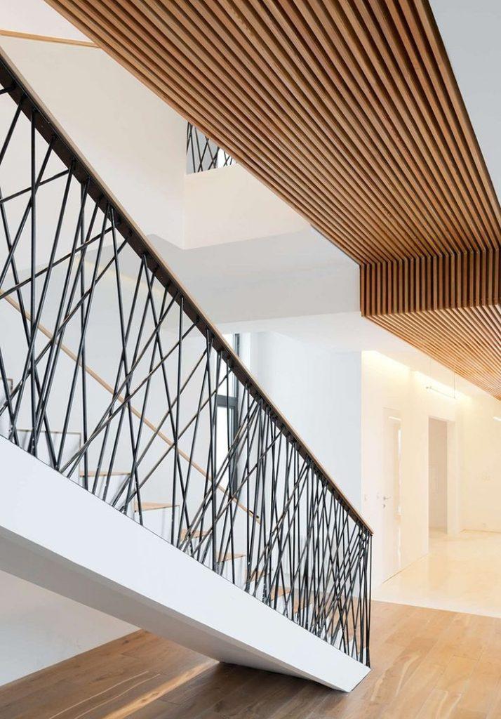 Stahltreppe mit extravagantem Stahlgeländer, Handlauf aus Holz, Wohnbereich